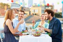 Groep Vrienden die Maaltijd op Dakterras eten Stock Afbeeldingen