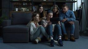 Groep vrienden die media op inhoud op tablet letten stock video