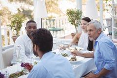 Groep vrienden die met elkaar samen interactie aangaan terwijl het hebben van lunch Royalty-vrije Stock Foto