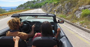 Groep vrienden die op de autosnelweg in rode convertibel draaien stock footage