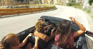 Groep vrienden die op de weg langs de kust in rode convertibel drijven stock videobeelden