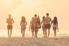 Groep vrienden die op het strand bij zonsondergang lopen Stock Afbeeldingen
