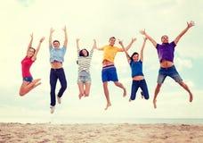 Groep vrienden die op het strand springen Stock Fotografie