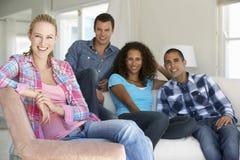 Groep Vrienden die op Sofa At Home Together ontspannen Stock Foto's