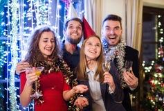 Groep vrienden die partij op Nieuwjarenvooravond hebben stock foto's