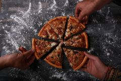 Groep vrienden die pizza eten Stock Afbeelding