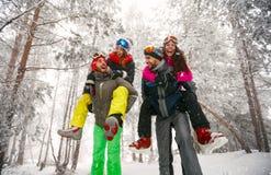 Groep vrienden die pret in bos op de sneeuw hebben Stock Afbeelding