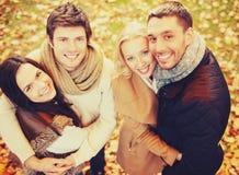 Groep vrienden die pret in de herfstpark hebben Stock Afbeeldingen