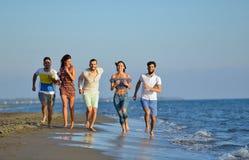 Groep vrienden die pret hebben die onderaan het strand bij zonsondergang lopen Royalty-vrije Stock Afbeeldingen
