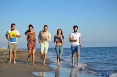 Groep vrienden die pret hebben die onderaan het strand bij zonsondergang lopen Royalty-vrije Stock Foto