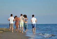 Groep vrienden die pret hebben die onderaan het strand bij zonsondergang lopen Royalty-vrije Stock Foto's