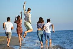 Groep vrienden die pret hebben die onderaan het strand bij zonsondergang lopen Stock Foto
