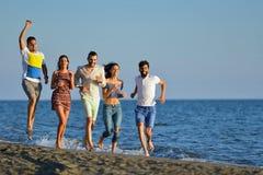 Groep vrienden die pret hebben die onderaan het strand bij zonsondergang lopen Royalty-vrije Stock Fotografie