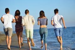 Groep vrienden die pret hebben die onderaan het strand bij zonsondergang lopen Royalty-vrije Stock Afbeelding