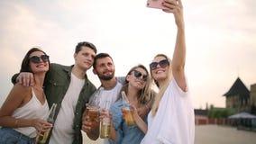 Groep vrienden die pret hebben die van een drank genieten en op het strand bij zonsondergang in langzame motie ontspannen Jonge m stock footage