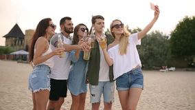 Groep vrienden die pret hebben die van een drank genieten en op het strand bij zonsondergang in langzame motie ontspannen Jonge m stock video