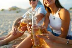 Groep vrienden die pret hebben die verfrist drank en ontspannend op het strand bij zonsondergang genieten van Jonge mannen en vro royalty-vrije stock afbeeldingen