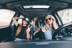 Groep vrienden die pret op de auto hebben Het zingen en het lachen in de autoaandrijving in stadscentrum stock afbeeldingen