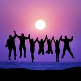 Groep vrienden die tegen zonsondergang springen Stock Foto's