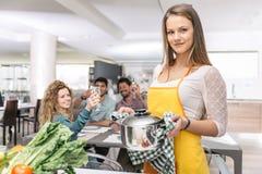 Groep vrienden die thuis diner koken samen te hebben Stock Afbeeldingen