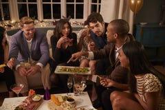Groep Vrienden die van Dranken en Snacks genieten bij Partij royalty-vrije stock afbeeldingen