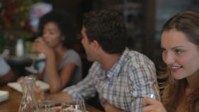 Groep Vrienden die van Maaltijd in Restaurant genieten stock footage