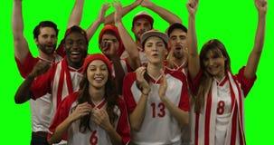 Groep vrienden die voetbal op spel letten stock footage
