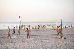 Groep vrienden die volleyball op het strand spelen Stock Afbeeldingen