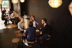 Groep vrienden die voor cappucinos in een koffiewinkel samenkomen stock fotografie