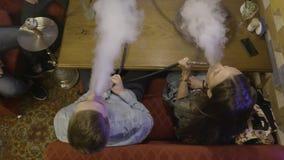 Groep vrienden die waterpijpen in waterpijp roken actie De vrienden ontspannen in waterpijprestaurant Kerel met het jonge vrouw d stock videobeelden