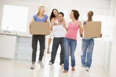 Groep vrienden die zich in nieuw huis bewegen Stock Fotografie