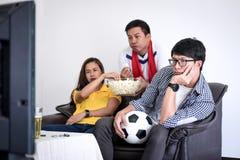 Groep vrienden fanclub het letten op voetbalgelijke op TV en cheerin stock foto's