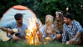 Groep vrienden het kamperen Zij hangen kampbrand rond, die gitaar spelen royalty-vrije stock fotografie