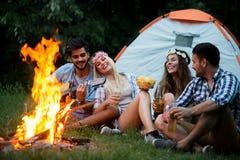 Groep vrienden het kamperen Zij hangen kampbrand rond, die gitaar spelen stock afbeelding