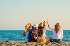 Groep vriendenspel op het strand stock afbeelding