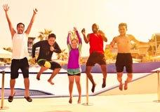Groep vriendensprong in de lucht stock foto