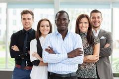 Groep vriendschappelijk zakenlui met mannelijke leider vooraan stock afbeeldingen
