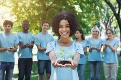 Groep vrijwilliger met bomen voor het groeien stock afbeelding