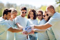 Groep vrijwilligers die handen op bovenkant in park zetten royalty-vrije stock afbeelding
