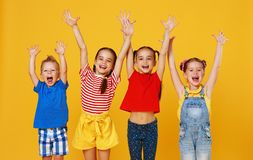 Groep vrolijke gelukkige kinderen op gekleurde gele achtergrond stock afbeeldingen