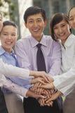 Groep vrolijke jonge bedrijfsmensen met handen bovenop elkaar Royalty-vrije Stock Foto's