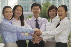 Groep vrolijke jonge bedrijfsmensen met handen bovenop elkaar Stock Foto's