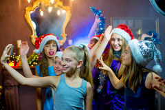 Groep vrolijke jonge meisjes die Kerstmis vieren Selfie Stock Afbeelding