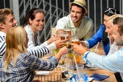 Groep vrolijke mensen die met dranken roosteren stock afbeelding