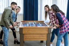 Groep vrolijke vrienden die lijstvoetbal spelen royalty-vrije stock afbeelding