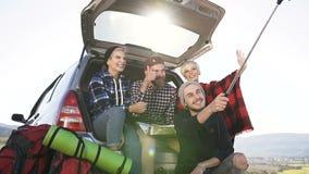 Groep vrolijke vrienden die selfie op smartphone, het zitten het leunen op boomstam van suvauto doen op bergachtergrond stock video