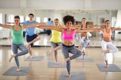 Groep vrouwen die de oefeningen van het lichaamssaldo doen stock foto