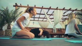 Groep vrouwen die yoga op de strand langzame motie uitoefenen stock videobeelden