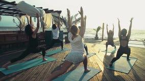 Groep vrouwen die yoga op de strand langzame motie uitoefenen stock footage