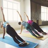 Groep vrouwen die zijplank doen bij de gymnastiek stock afbeeldingen